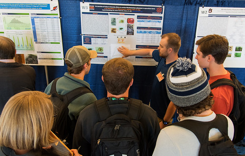 A student researcher displays his poster to several students.