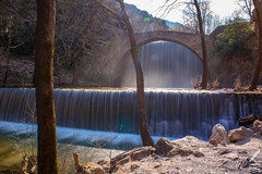 "Waterfalls beneath a very old arched bridge at Palaeokaryá, near Trikala, Greece.  There is a dreamy, emotive element emerging from the scenery, despite the winter weather. The clear waters of Portaïkós river can inspire and cleanse…  The scenery reminds us of a poem written by the romantic as well as metaphysical poet of the 17th century:  ""With what deep murmurs through time's silent stealth Doth thy transparent, cool, and wat'ry wealth Here flowing fall, And chide, and call, As if his liquid, loose retinue stay'd Ling'ring, and were of this steep place afraid;…""  —Henry Vaughan (The Waterfall)"