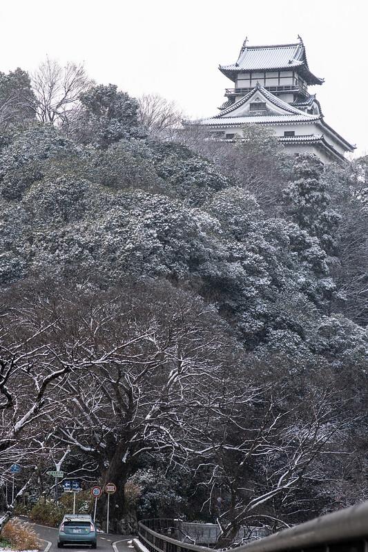 雪が降る犬山城と自動車