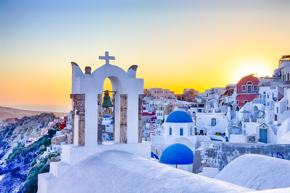 Picturesque Citiscape of Oia Village Houses and Classic Church with Bell Located on Volcanic Caldera Hills on Santorini Island During Sunset