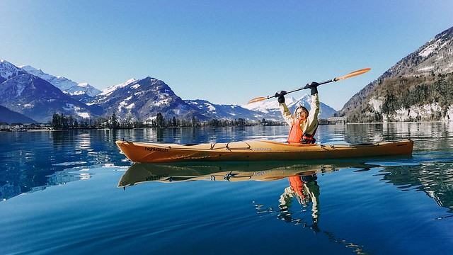 I girl sits in a kayak on a large blue lake surrounded by mountains covered in snow.