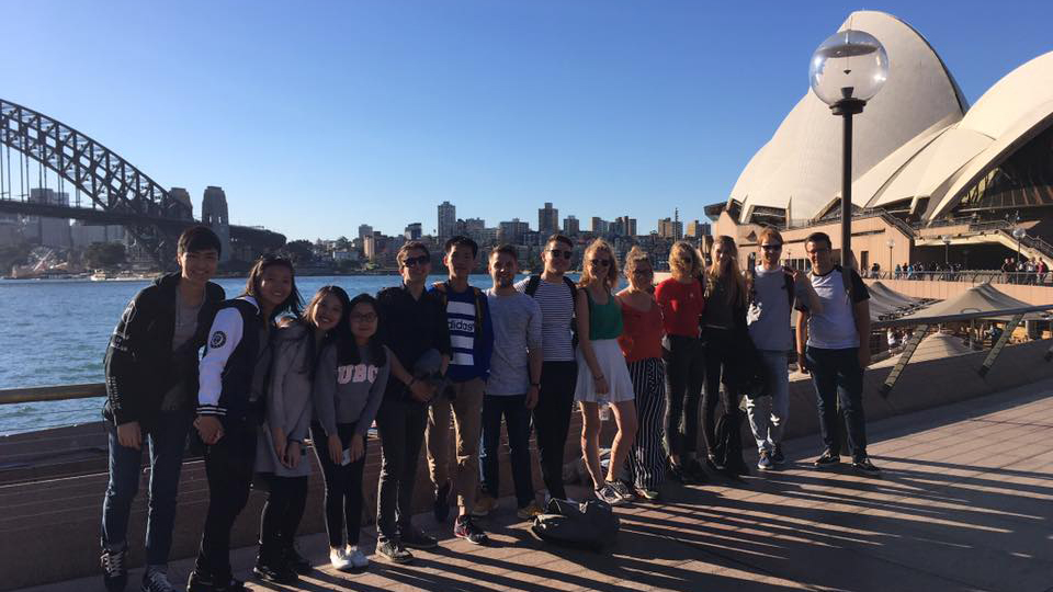 Emma Robinson stands with a group of students in front of the Sydney Opera House and Sydney Harbour Bridge.
