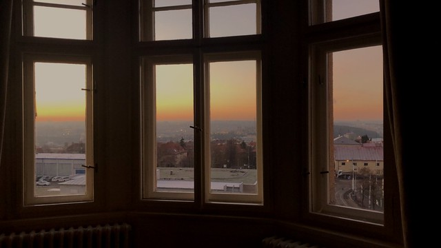 A view of sunset coming over a skyline of houses and small buildings from a large bay window.