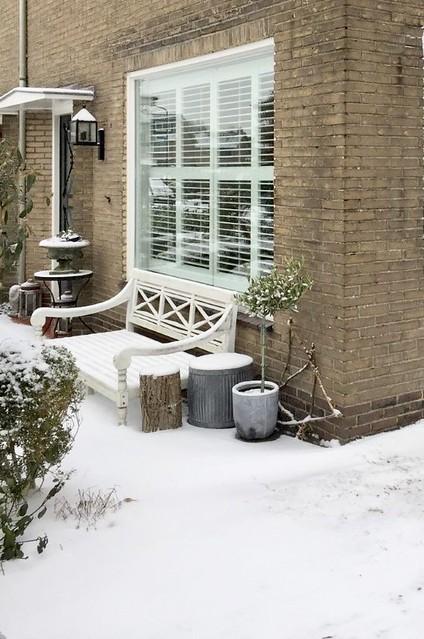 Witte tuinbank tegen voormuur