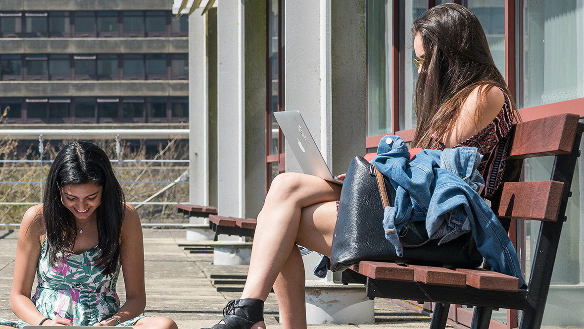 Two female students looking at their laptops - one on the left sat cross-legged on the floor and one sat on a bench on the right
