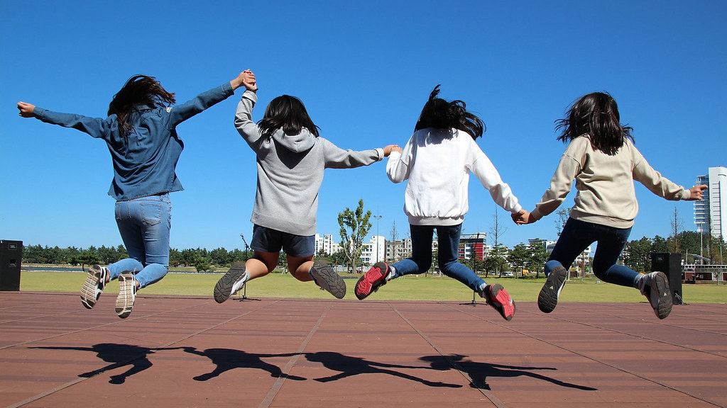 A group of young girls jumping in the air for fun