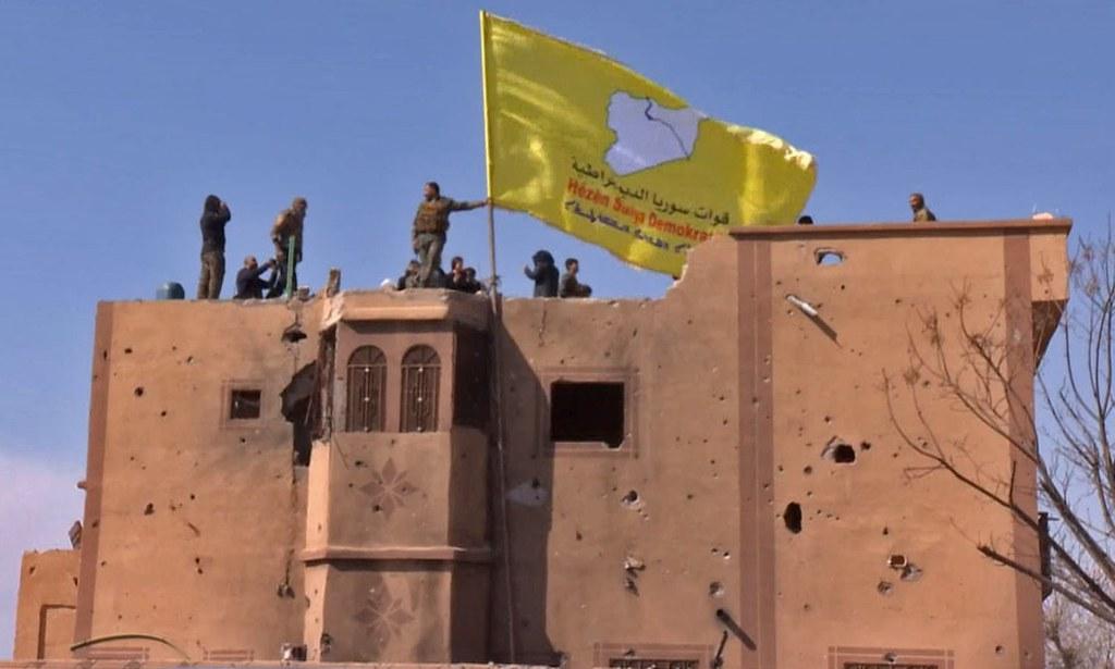 美國支持的武裝勢力「敘利亞民主力量」於巴古斯村樹立旗幟。(圖片來源:Ronahî TV/AFP/Getty Images)