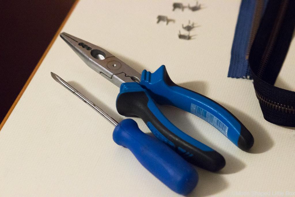 ruuvimeisseli, pihdit, vetoketjun korjaaminen, lukon vaihto vetoketjuun