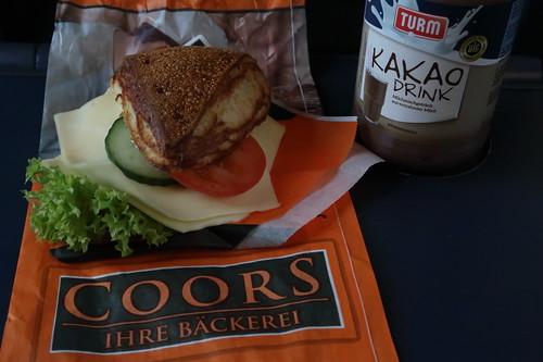 Vegetarisch belegte Laugenecke von der Bäckerei Coors (Osnabrück Hbf) mit Kakao Drink als Frühstück auf Zugfahrt nach Hamburg