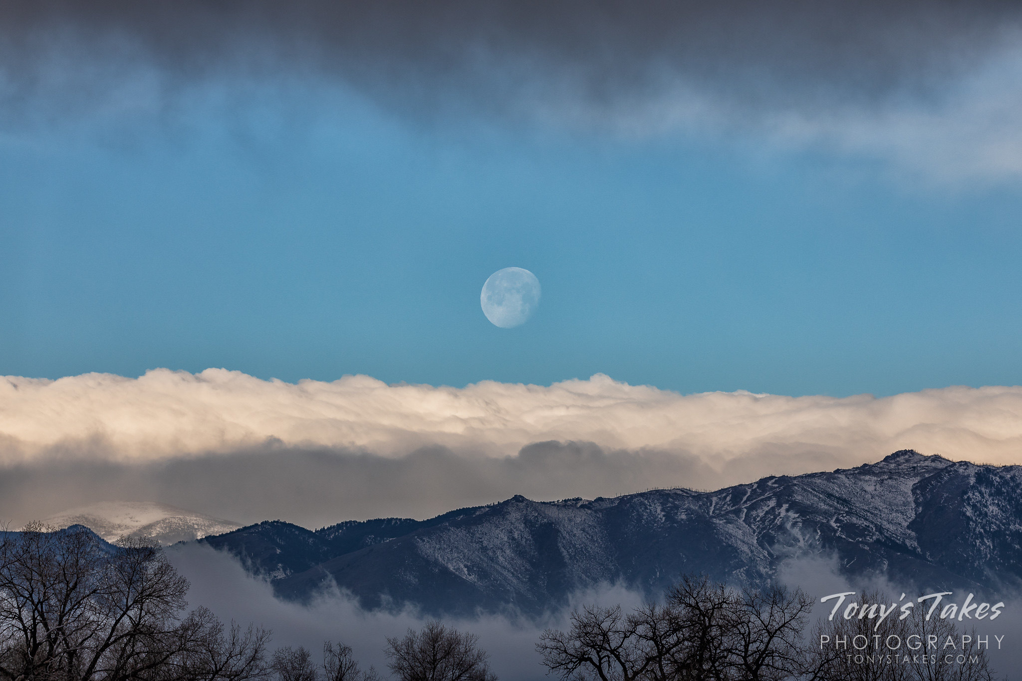 The moon sets over the Colorado Front Range foothills with clouds both above and below.  (© Tony's Takes)