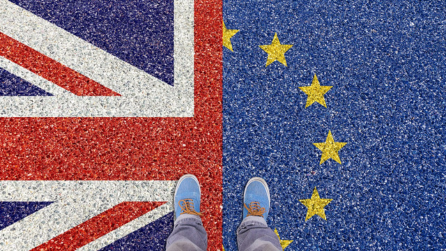An image of a person stood on both the Union Jack and the European Union flag
