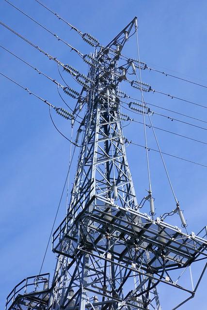 Transmission Tower_Omiya_(2019_02_24)_1_resized_1 高圧送電用鉄塔を下から見上げて撮影した写真。 青空を背景に鉄塔が伸び、多数の碍子が取り付けられている。