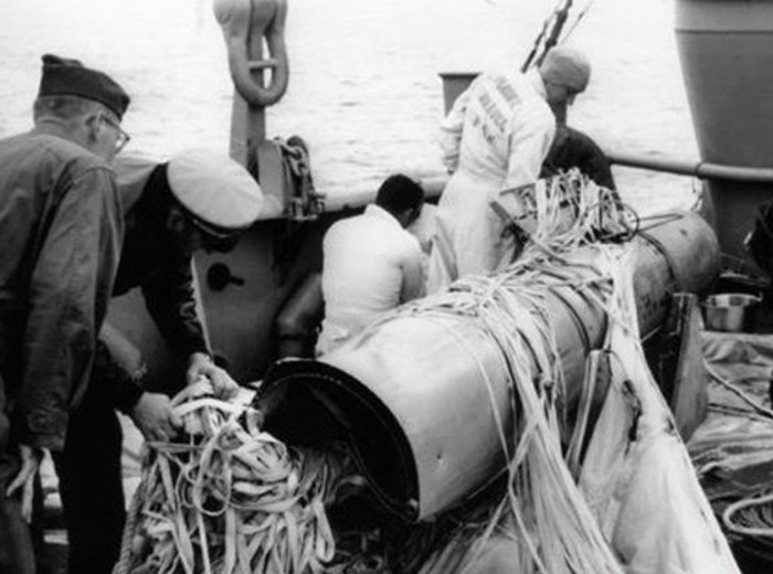 Three sailors inspect a weapon on the deck of a ship.