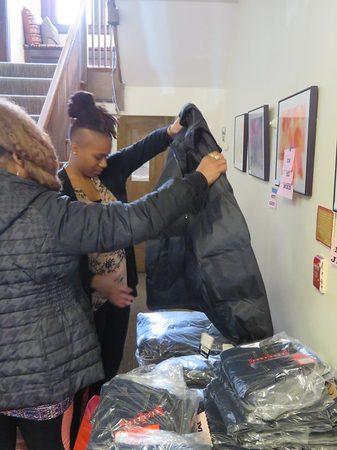 A photo of two women holding up clothing in front of a table of clothes in various sizes and colors wrapped in plastic.