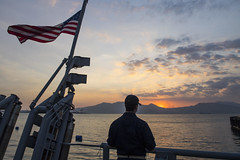 Ensign Alexander Mobilia observes the sunset aboard USS Pioneer (MCM 9) after the ship pulled into Subic Bay, March 21. (U.S. Navy/MC2 Joshua Mortensen)
