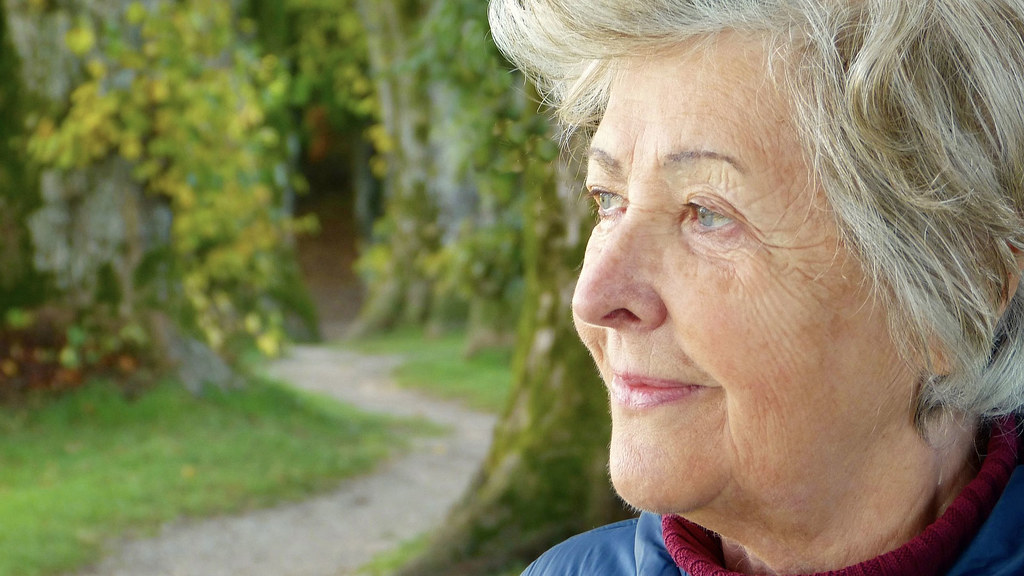 An older woman looks wistfully off camera