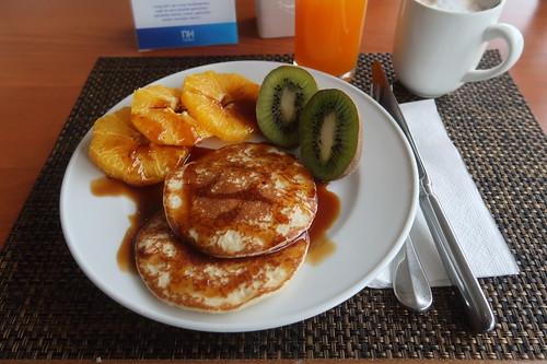 Pfannkuchen mit Zuckersirup, Orangenscheiben und aufgeschnittenen Kiwi