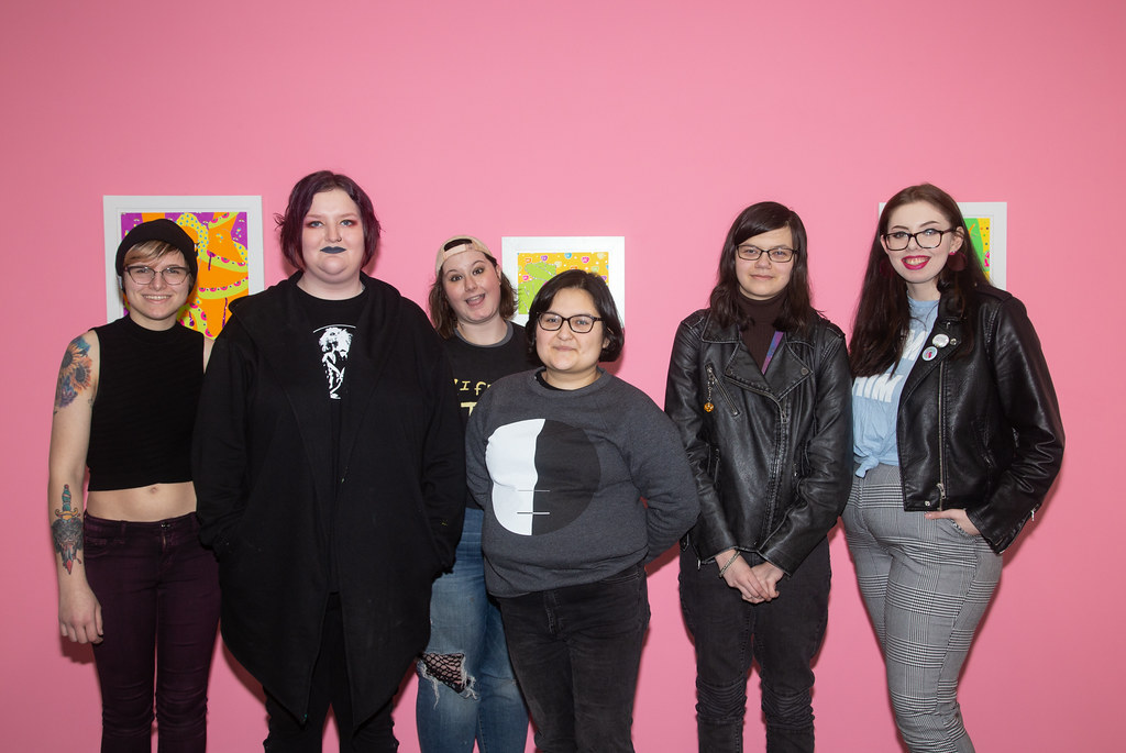 photograph of all artists included in Tongue N Cheek exhibition standing in front of a pink wall.