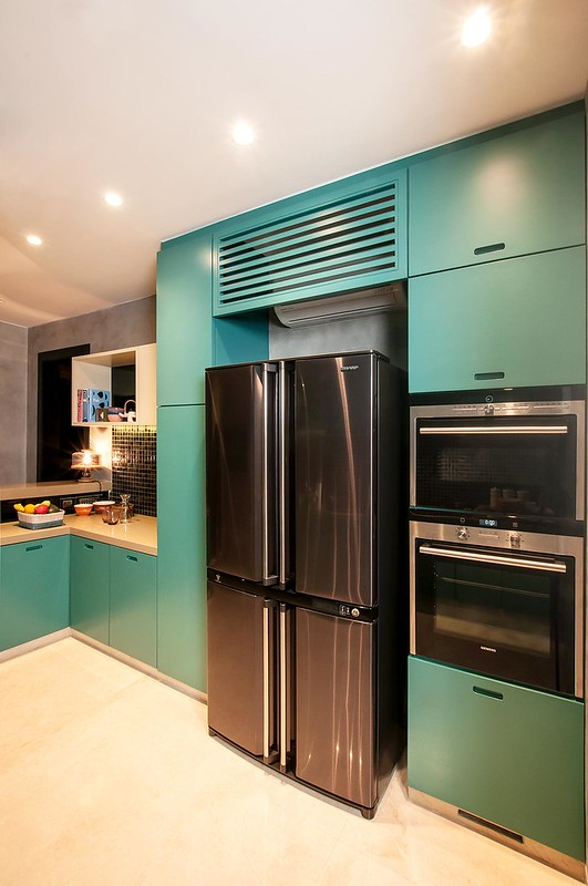 a teal kitchen with built-in appliances