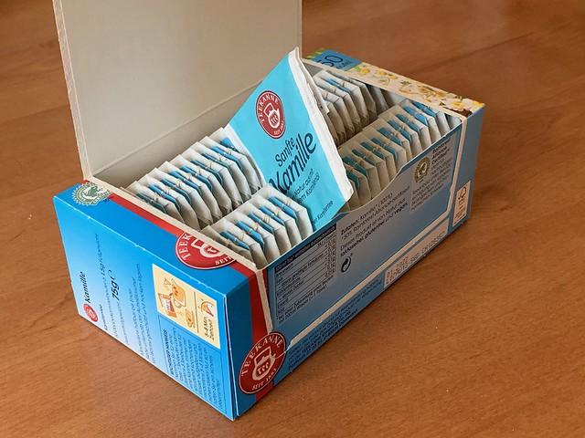 Packung mit Teebeuteln und einem einzelnen, zwischen die Teebeutel gesteckten Teebeutelbriefchen (Einzelverpackung für Teebeutel)