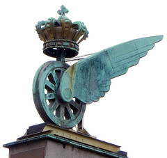 Sculpture of a winged wheel with a crown, made of weathered copper (verdigris), in Copenhagen, Denmark
