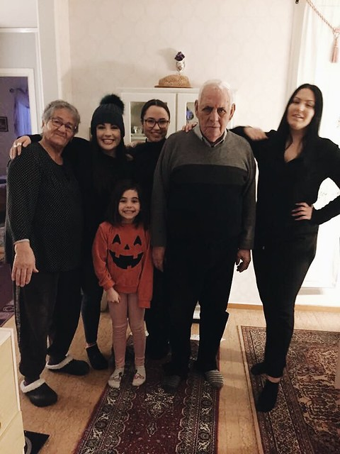 A family posing and smiling together in a room.