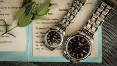 Couple's watches on a wedding invitation