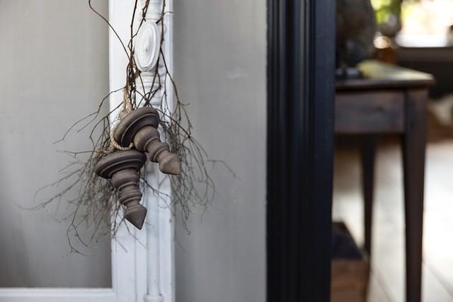 Houten klosjes met takjes aan deurklink