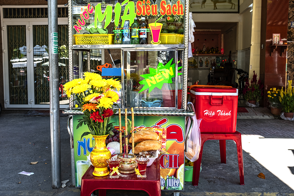 Offerings to the spirits at sugarcane juice stand--Saigon