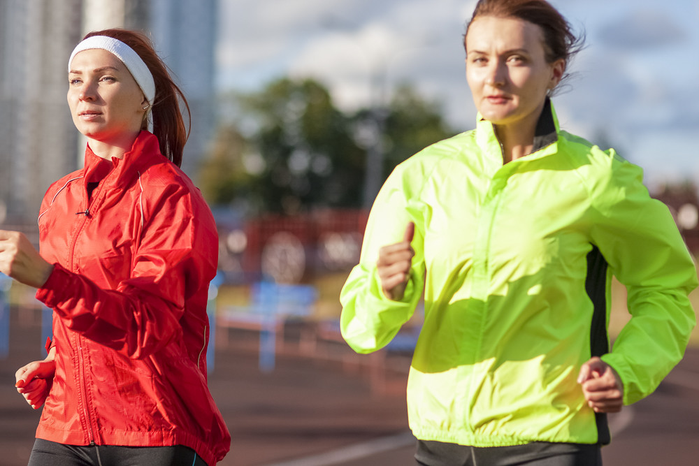 Sport and Athletics Concepts.Two Caucasian Females having Jogging Excercises Outdoors