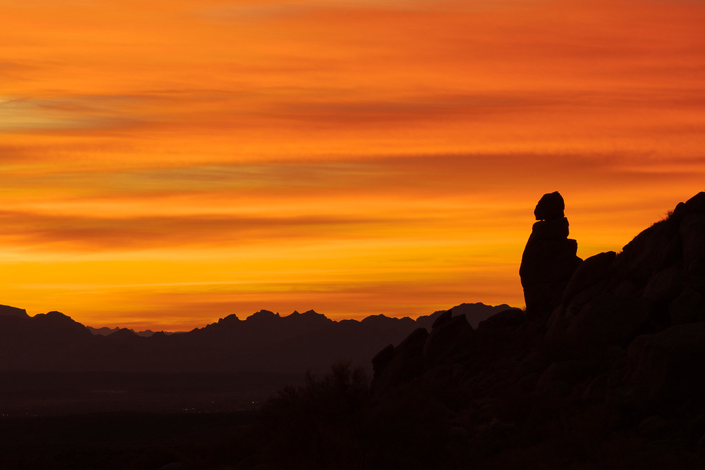 A rock formation sits before orange clouds at sunrise along the Marcus Landslide Trail in McDowell Sonoran Preserve in Scottsdale, Arizona
