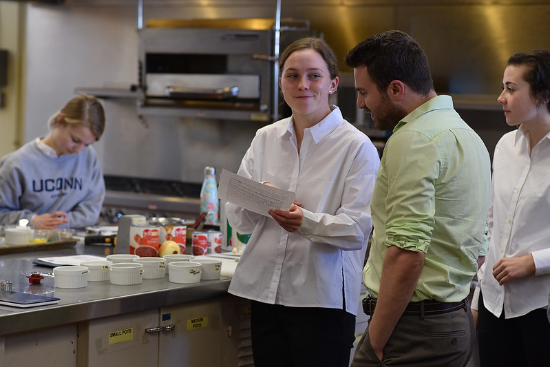 Students in Food Service Systems Management lab (NUSC 3271) prepares a recipe revamped to improve its nutritional profile while lab supervisor Michael Comperatore (in the green shirt) looks on.