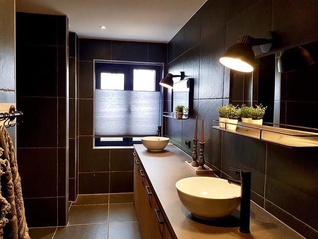 Donkere badkamer met houten wasmeubel