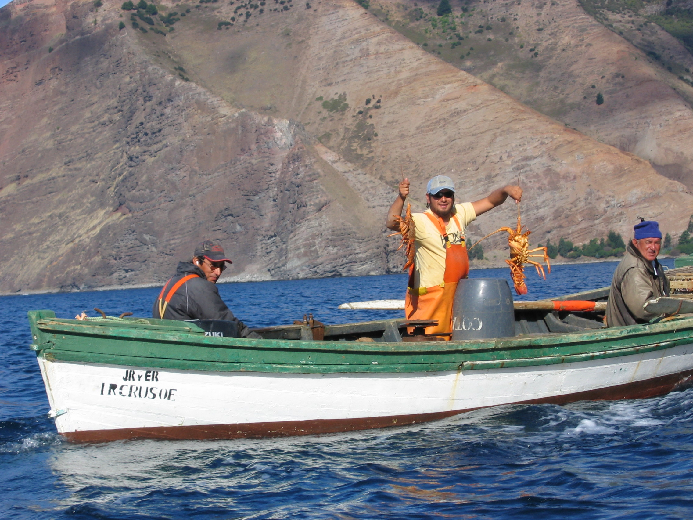 A fisherman with two spiny lobsters off Robinson Crusoe Island, Chile. Photo taken on April 15, 2005.