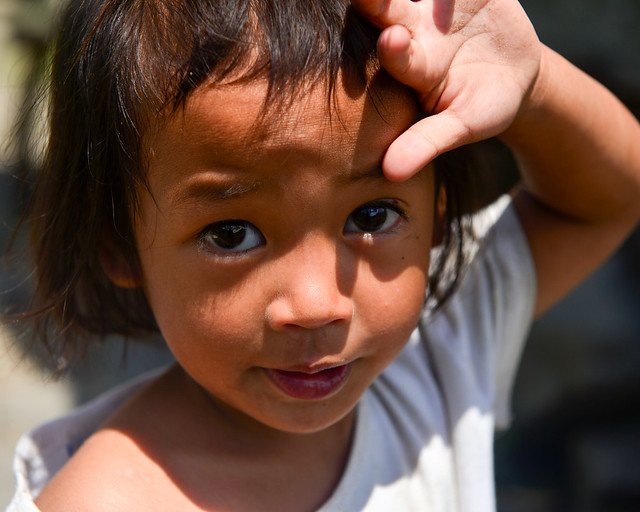 Niño tapándose del sol con la mano en la aldea de Batad