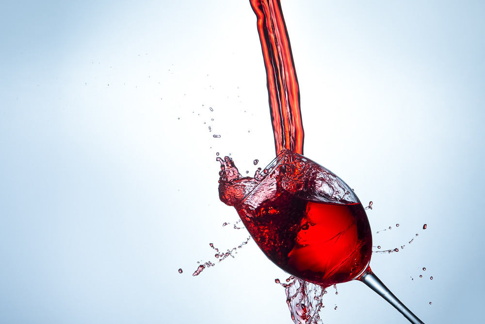 Fast Action Photography. Streams and Droplets of Red Wine Pouring Out of Clear Wine Glass.
