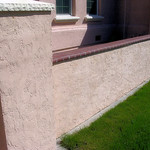 Block wall with brick cap and stucco.